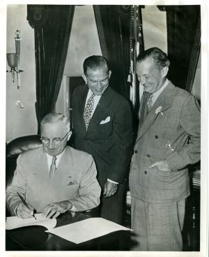 President Truman signs the Fulbright Act Aug 1, 1946, #015, as Senator Fulbright, center, and Assistant Secretary of State for Public Affairs, Benton, beam.